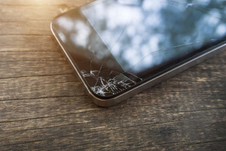 Broken screen of black smart phone. Stock Photo