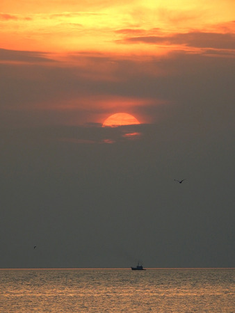 Sunset and  lonely boat at thailand sea.