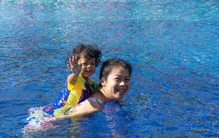 Asian child boy learn swimming in a swimming pool with mom. - Sunset filter effect. Banque d'images