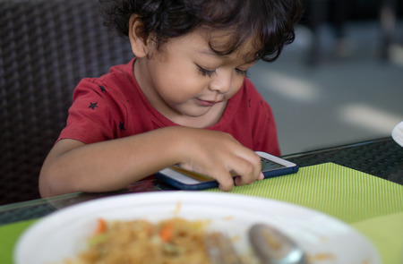 Boys do not eat food because they play smartphones. Stock Photo