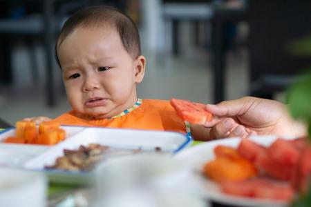 Schattige Aziatische babymeisje van 5-6 maanden wil geen watermeloen eten.