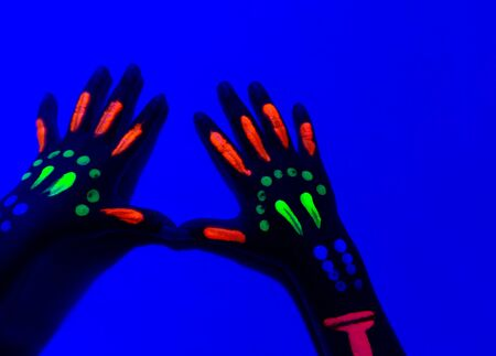 Close-Up Of Neon Painted Hand Against Blue Wall. Фото со стока
