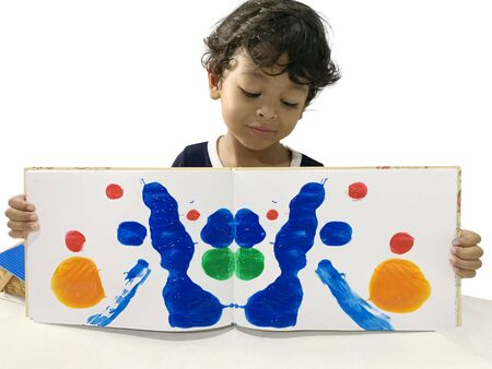 Asian boys are showing art from using paint on the book and then fold to create a picture. 版權商用圖片