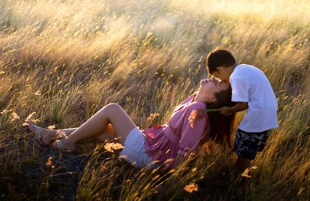 The son showed love for his mother. By kissing on the forehead of the mother at the meadow in the evening