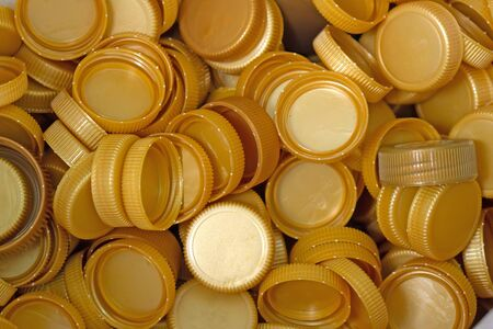 The gold plastic lid that is left over from the bottles are collected to be recycled into other items for reuse.