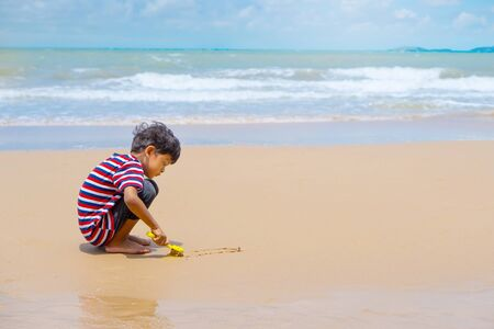 Little asian boy play with toy and sand on the beach. Reklamní fotografie