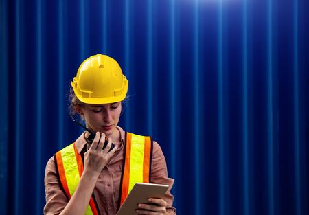 Female foreman is using walkie talkie and computer tablet to control work in industrial business