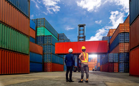 Engineer and industrial workers Women look Forklift truck handling container box in shipping industry and cargo business at at warehouse yard.