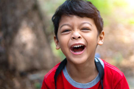 A boy wearing a red shirt laughed happily