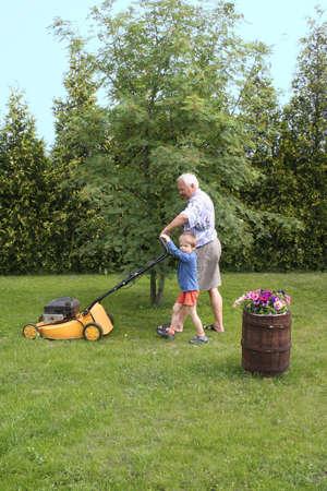 Grandfather and grandson mowing grass Standard-Bild