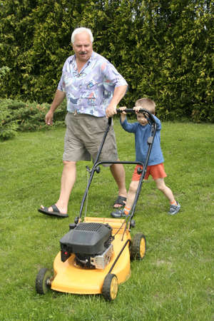 mowing grass: Grandfather and grandson mowing grass Stock Photo