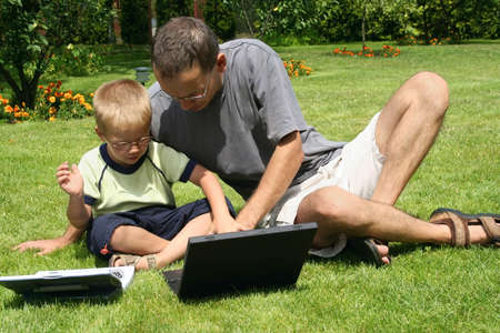 boy and his fathers working on laptops on grass photo