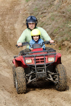 race relations: Dad with son riding a quad bike