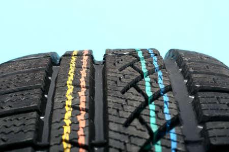 Brand new winter tire pattern on blue background photo