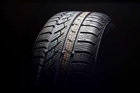 Brand new winter tire pattern on black background photo