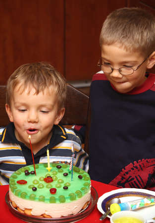 Two boys is blowing candles on birthday cake photo