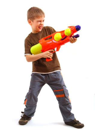 Young boy with water gun over white background. Standard-Bild