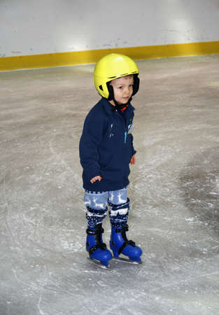 to stumble: winter time. Young boy learning to skate  Stock Photo