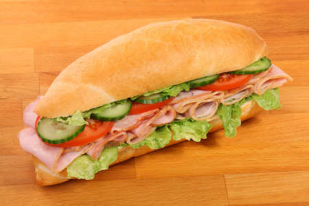A large ham and tomato sandwich, on a wooden board photo