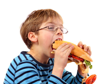 boy eating large sandwich on white background
