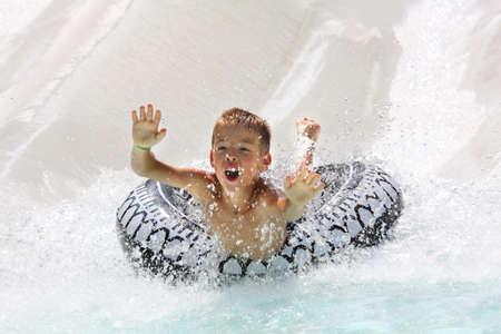 tobogan agua: Un ni�o que se divierten en parque acu�tico  Foto de archivo