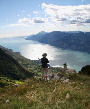 Alone man overview Lake Garda with Monte Baldo mountain, Italy.  photo