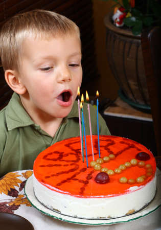 Young boy is blowing candles on birthday cake  photo