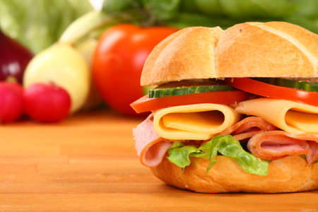 Delicious ham, cheese and salad sandwich, on a wooden board  Standard-Bild