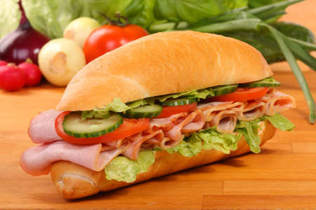 Delicious ham, cheese and salad sandwiches on a wooden board