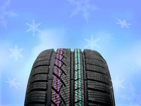 Brand new winter tire on winter frozen background Stock Photo - 16447981