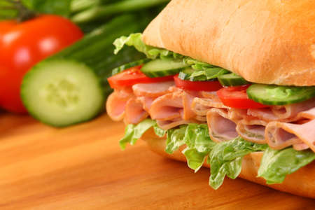 Fresh ham sandwich on wooden board - close up