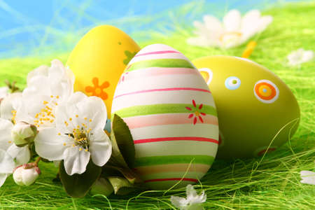 Colorful Easter Eggs and Flowers on Green Grass photo