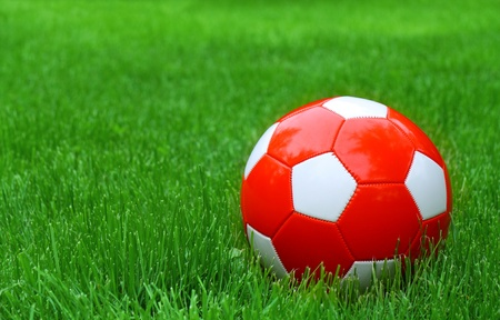 Red and white soccer football and green grass