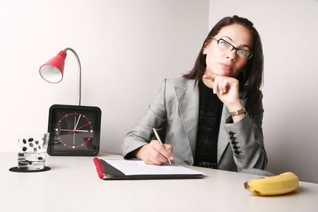 Good looking adult woman working at the office. Probably waiting for lunch... Stock Photo - 2833401