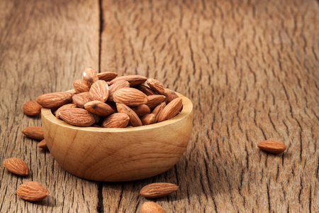 Closeup almonds kernels in wooden bowl with hemp sack on rustic wooden background .