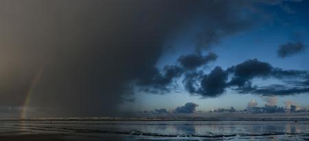 waders: Arco iris aparece en una tormenta inminente. Ocean Shores, Washington. Foto de archivo