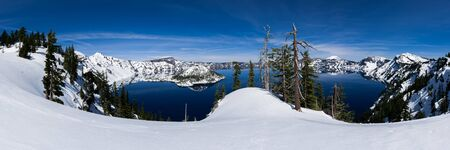 crater lake: Panoramic of Crater Lake with snow on a sunny day. Stock Photo