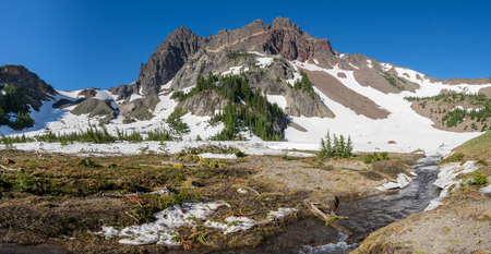 Snow melts at the base of Three-Fingered Jack and forms the headwaters of Canyon Creek. Mt Jefferson Wilderness, Oregon Stock Photo