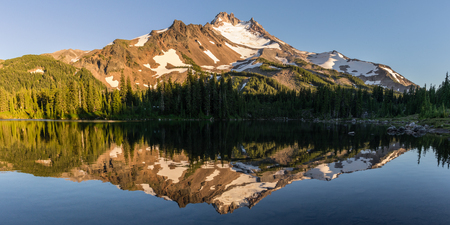 At 10,492 feet high, Mt Jefferson is Oregons 2nd tallest mountain.  Reflected here in Scout Lake at sunset. Mount Jefferson Wilderness Area, Oregon. Stock Photo