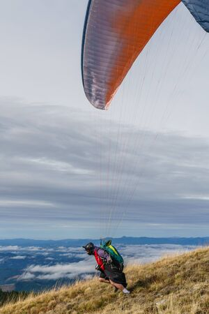 Paraglider running downhill to launch himself into the sky.