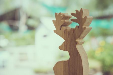 Wooden deer beside window coffee shop with nature garden background 写真素材