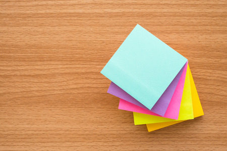 Stack of color paper notes on wood table with copy space