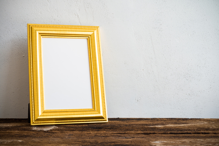 Golden vintage photo frame on old wooden table over white wall background