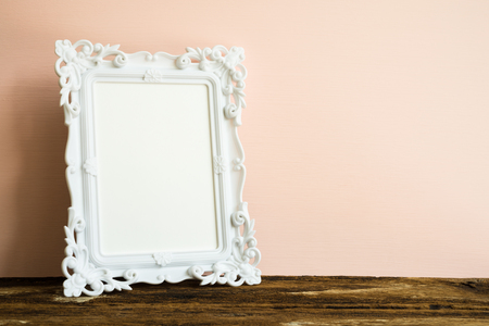 White vintage photo frame on old wooden table over pink wall background