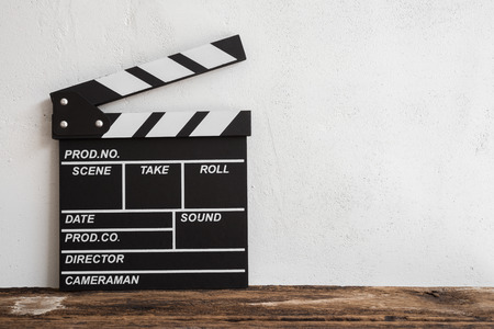 Cinema clapperboard on wooden with white wall concrete background - Movie entertainment concept