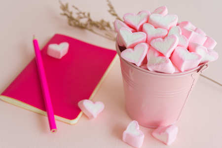 Fluffy pink heart marshmallow in small tank and pink notepad, pencil on pink background Archivio Fotografico
