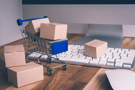 Online internet global purchases transportation business, cardboard boxes, trolley on table with keyboard, mouse and desktop computer, e-commerce online shopping and logistics shipping import export concept Фото со стока