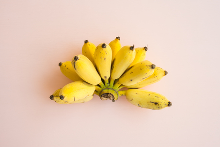 Flat lay of banana bunch on pink background - Creative ideas summer holiday concept