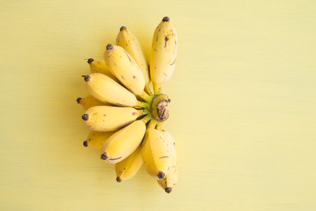 Flat lay of banana bunch on yellow background - Creative ideas summer holiday concept