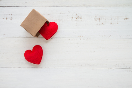 Two red hearts go out paper box on white wooden background - valentines day concept
